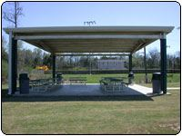 Covered picnic pavilion with picnic tables and cement floor, in grassy field