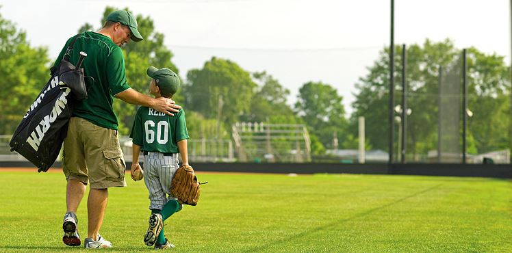 Baseball, image of man with young boy in baseball uniform walking on field