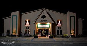 Oak Mountain Emporium, one story cream building, at night, with lit Christmas trees in the windows